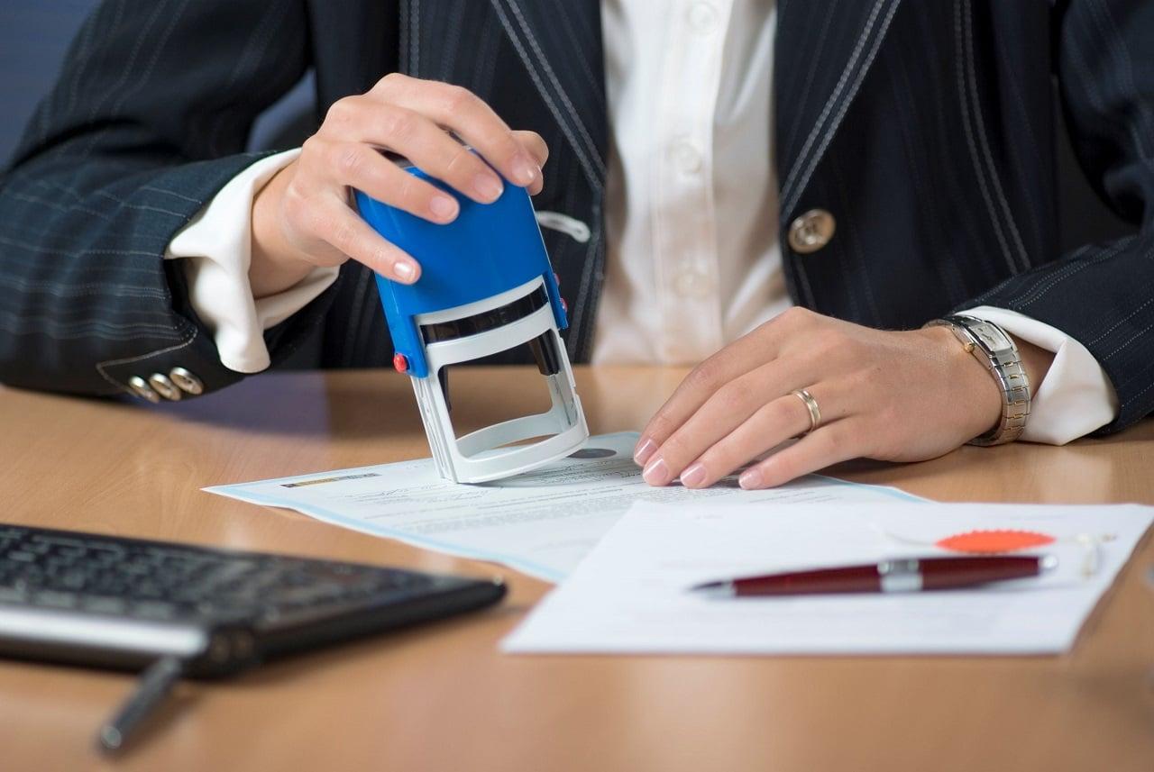 Notaire signant un acte notarié